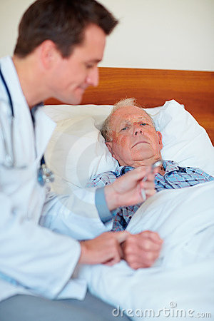 Senior man getting his pulse checked by a doctor