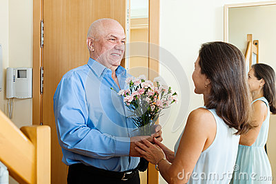Senior man giving bunch of flowers to  woman