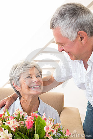 Senior man giving his partner a bouquet of flowers