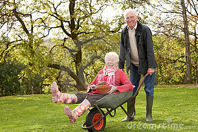 Senior Man Giving Woman Ride In Wheelbarrow