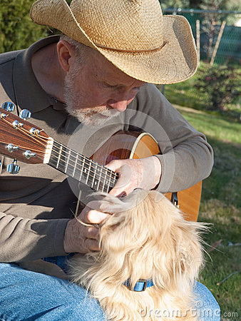 Senior man with guitar petting dog