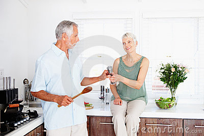 Senior man helping wife by cooking food