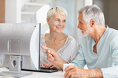 Senior man helping wife to use computer