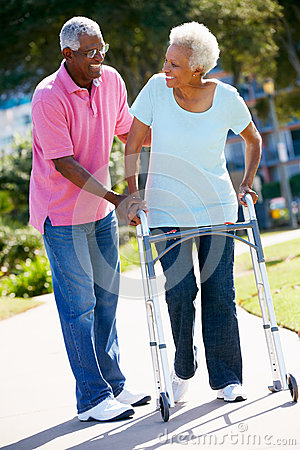 Senior Man Helping Wife With Walking Frame