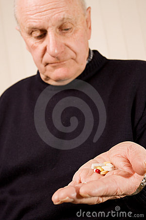 Senior man holding group of tablets or pills