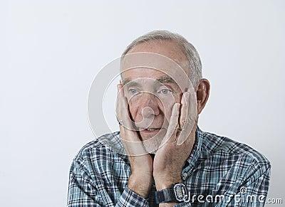 Senior man holding head in hands