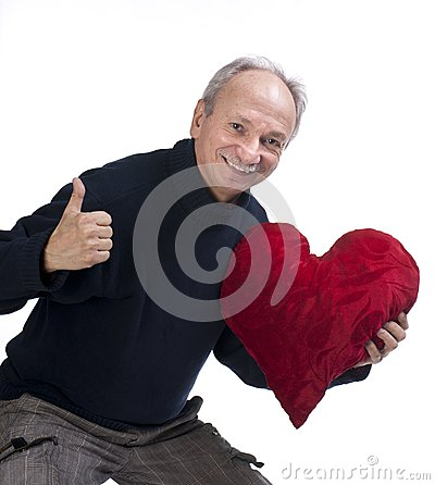Senior man holding heart pillow and showing yes sign