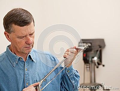 Senior man holding a metal saw