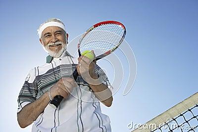 Senior Man Holding Tennis Racquet And Ball