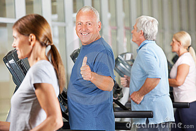 Senior man holding thumbs up in gym
