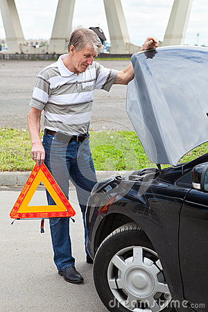 Senior man holding warning sign near car