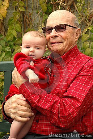 Senior man holds grandbaby in red as they smile