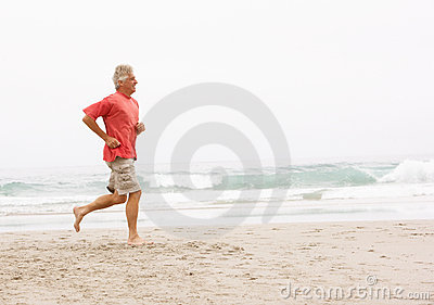 Senior Man On Holiday Running Along Beach