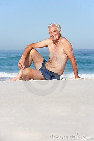 Senior Man On Holiday Sitting On Beach