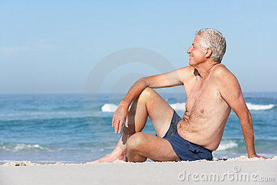 Senior Man On Holiday Sitting On Sandy Beach