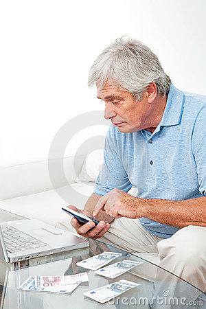 Senior man at home with calculator
