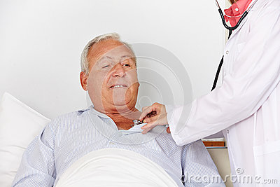 Senior man in hospital bed getting