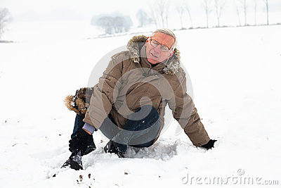 Senior man with injured leg on snow