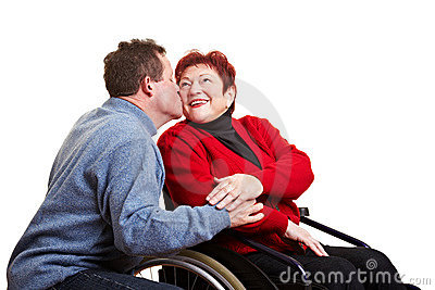 Senior man kissing his disabled