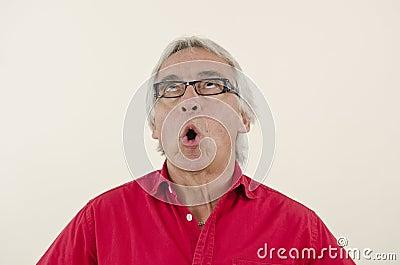 Senior man looking surprised upwards