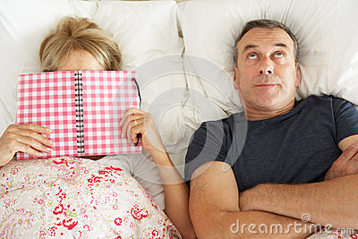 Senior Man Lying In Bed Next To Senior Woman