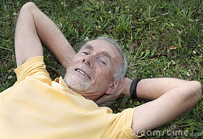 Senior man lying on grass contented