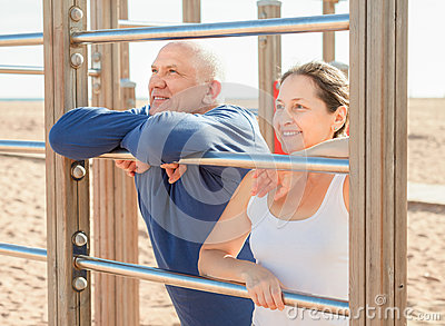 Senior man and mature woman training at playground