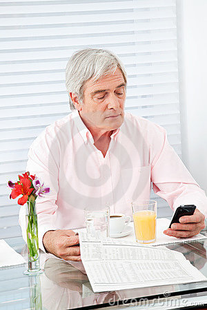 Senior man with newspaper and cell