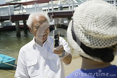 Senior man photographing wife using camera phone outdoors