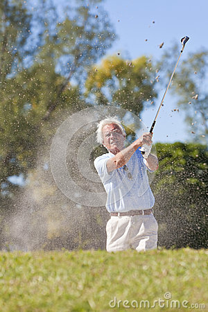 Senior Man Playing Golf Shot In a Bunker