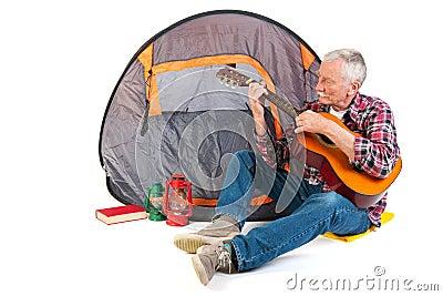 Senior man playing guitar by tent