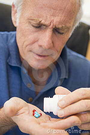 Free Senior Man Pouring Pills Out Of Bottle Stock Photography - 7769802