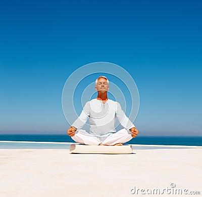 Senior man practicing yoga at the beach