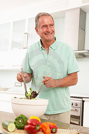 Senior Man Preparing Salad In Modern Kitchen