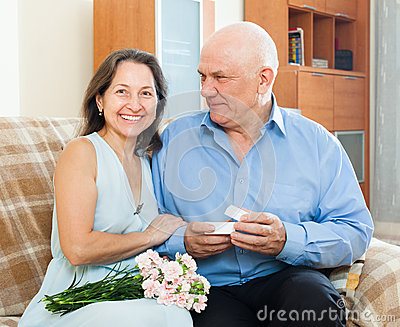 Senior man presenting smiling mature woman jewel