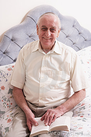 Senior Man Reading Book On Bed