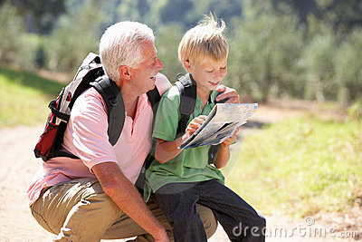 Senior man reading map with grandson on country wa