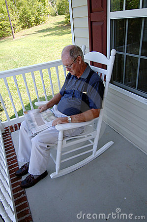 Senior man reading newspaper on front porch