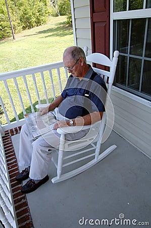 Free Senior Man Reading Newspaper On Front Porch Royalty Free Stock Image - 6829366