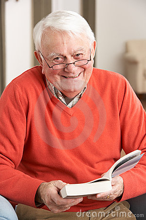 Senior Man Relaxing In Chair At Home Reading Book