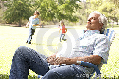 Senior Man Relaxing In Park With Grandchildren