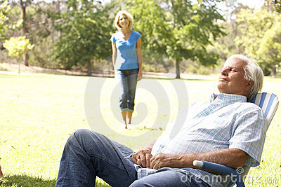 Senior Man Relaxing In Park With Wife