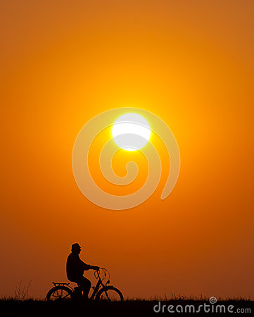 Senior man riding bicycle at sunset