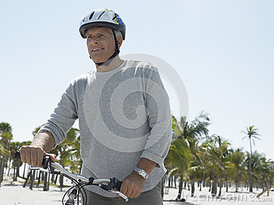 Senior Man Riding Bicycle On Tropical Beach