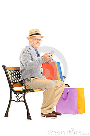 Senior man seated on a bench holding bags and typing a sms