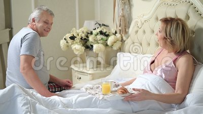 Senior man serving breakfast to woman in bed stock video