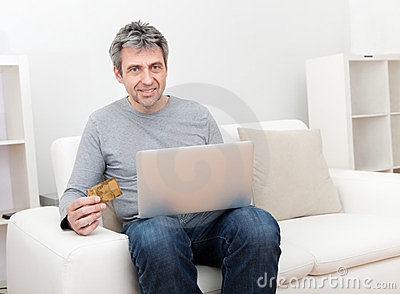 Senior man shopping at home using laptop