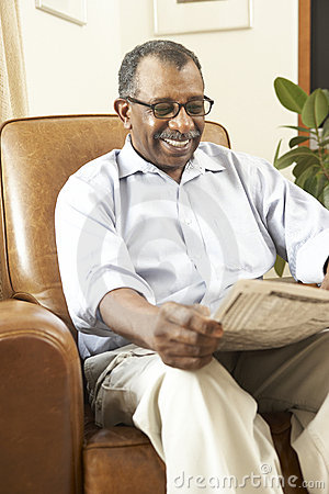 Senior Man Sitting In Armchair Reading Newspaper