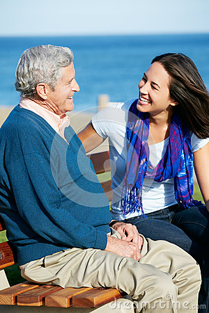 Senior Man Sitting On Bench With Daughter