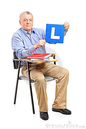 A senior man sitting on a chair holding a L plate